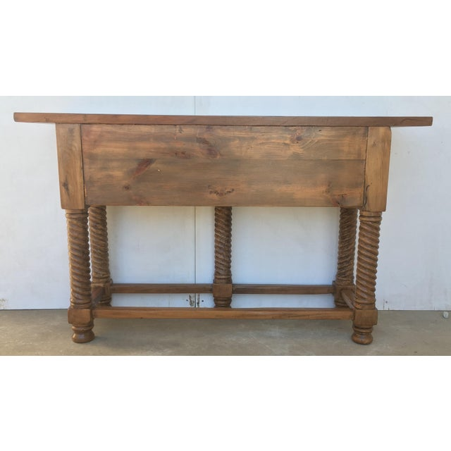 About A 19th century walnut console table with a slab top above a frieze with two drawers with front decorated with carved...