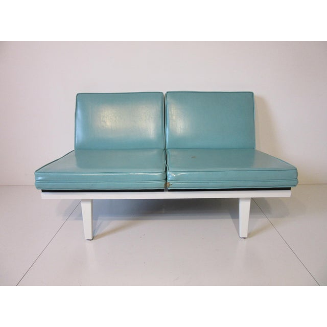 A two cushion Nelson Steelframe loveseat with white metal frame, turquoise cushions and adjustable feet. Manufactured by...