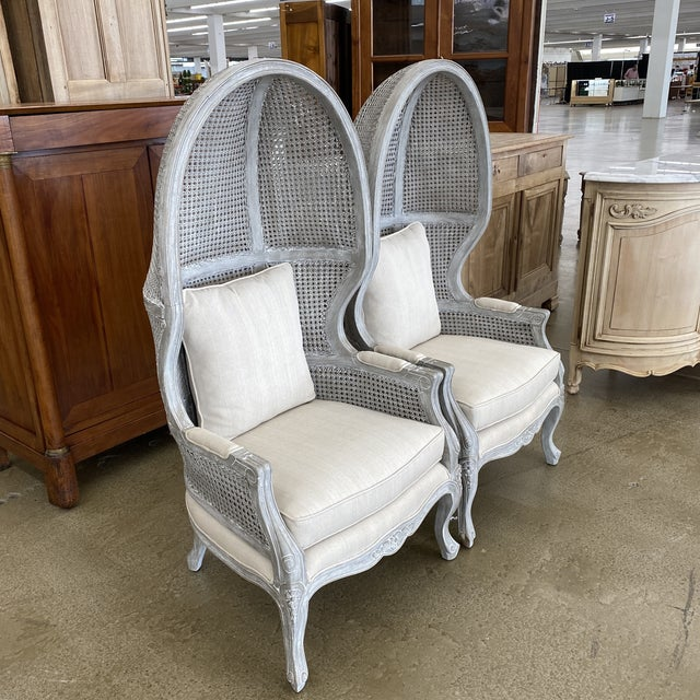 Pair of French Louis XVI style hooded balloon porters chairs with double caned bonnet. Classic chair features a very...