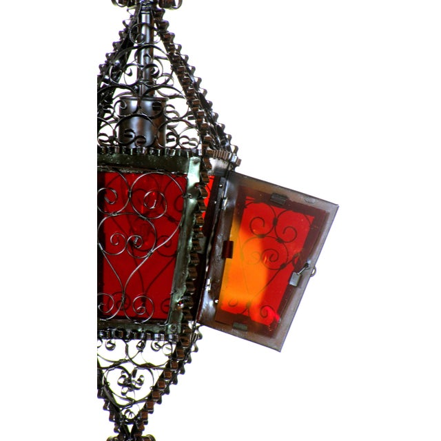 Handmade wrought iron lantern with a single light. Red glass panels.