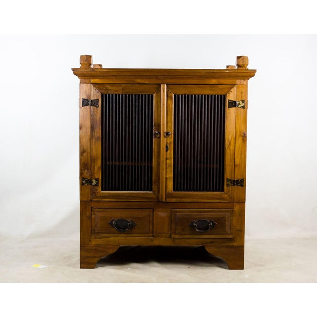 Storage and design are paired perfectly with this vintage custom Indonesian iron and wood cabinet. This piece was custom...