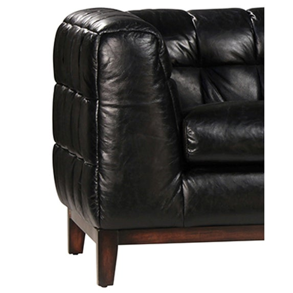 Aged leather sofa with wood frame legs. This sofa is classic with an edge in its jet black color.