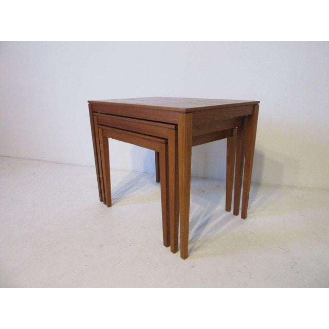 A set of three teak wood nesting tables with well grained tops and tapering legs, made in Denmark and designed by Bent...