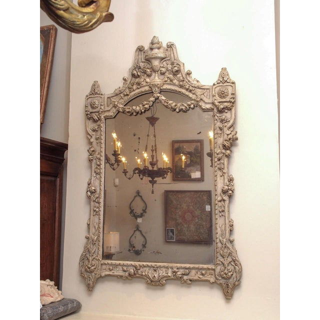 A beautifully carved 19th century French mirror, the arched top centered with a tall urn, with flowered garlands extending...