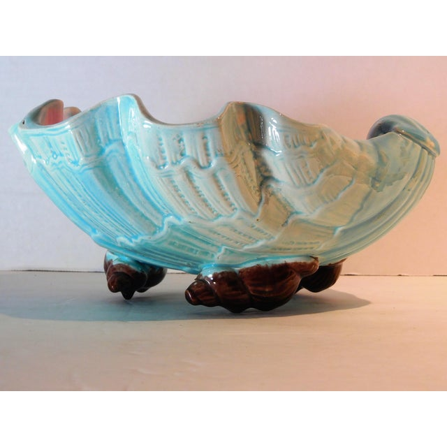 This Majolica bowl in the shape of a large clam shell bottom, has an aqua exterior and a pale pink interior and sits of...