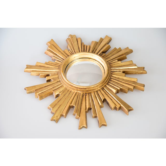 A beautifully carved Mid 20th-Century French giltwood sunburst mirror with the original convex glass. The lovely gilt...
