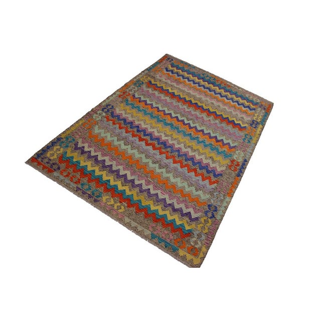 Add a touch of elegance to your home with this casual chic handwoven tribal Kilim wool rug. Constructed on a loom by nomad...