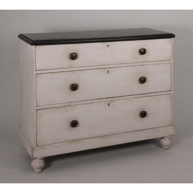 An antique English country painted pine chest of drawers with a restored, distressed finish in white and black . The black...