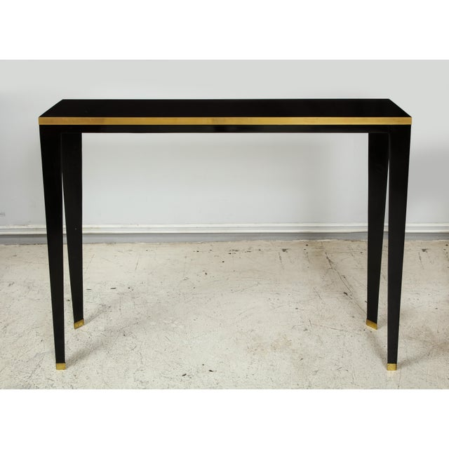 Custom ebonized brass-banded consoles on tapered legs Measures: H 36.5 in. x W 47 in. x D 11.5 in. Additional Options This...
