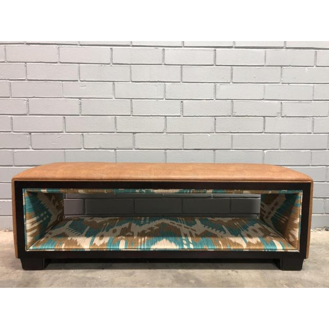 The Margaux Bench is a first quality showroom sample that features a brown leather with a teal and brown patterned fabric.