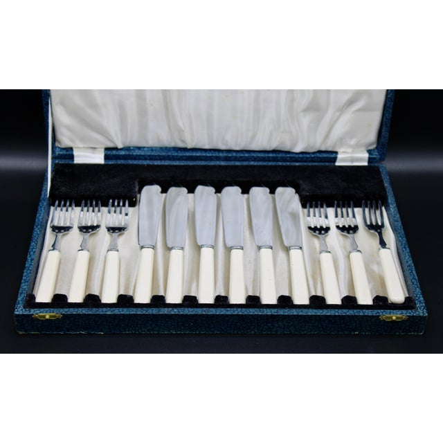 A superb set of white Bakelite handled chrome plated silverware, circa 1940. Includes 6 forks, 6 knives, and original box...