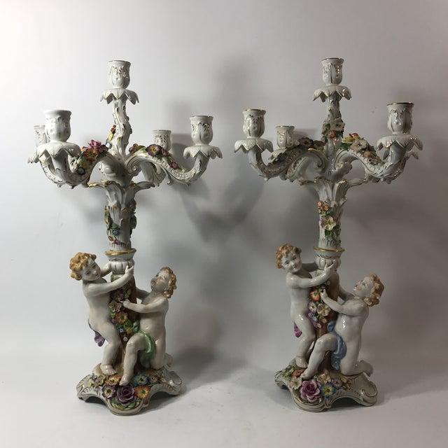 A pair of figural porcelain candelabras by Von Schierholz. Features two nude putti figurines wrapped around the tree trunk...
