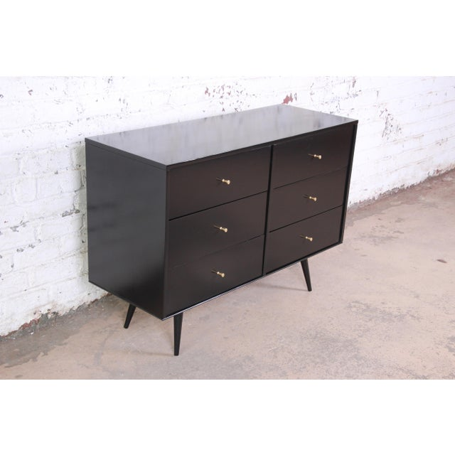 An excellent six drawer black lacquered Planner Group dresser by Paul McCobb. The dresser sits upon splayed legs and...