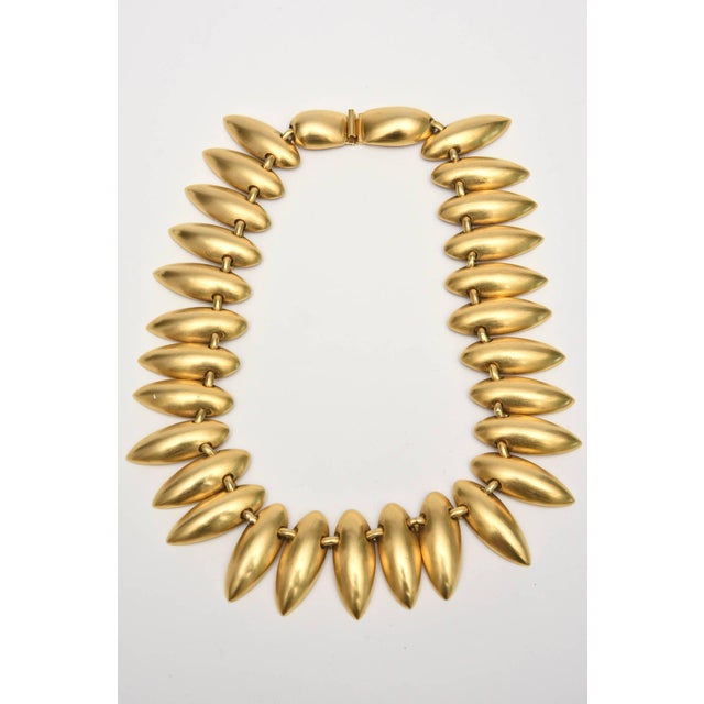 This beautiful set of a gold plated necklace and clip on dangle earrings is in the style of Robert Lee Morris and his...