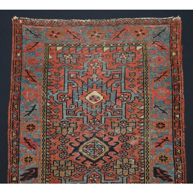 Offered is an antique Persian Karaja rug featuring a triple medallion geometric pattern. The main color is brick while...