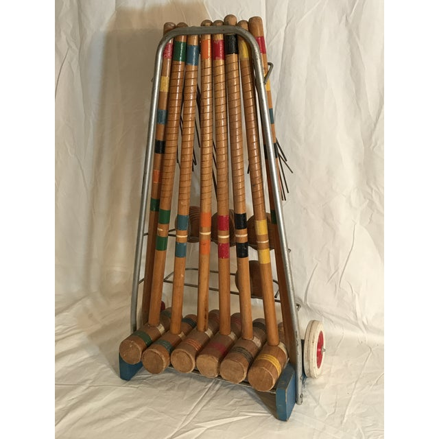 A complete croquet game set, circa 1950's. This vintage croquet game set includes a metal and blue painted wood rolling...