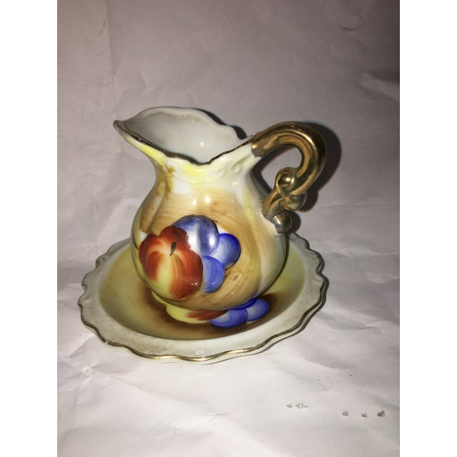 A Small Decorative Porcelain creamer and dish with fruit decorations and gold trim. Very attractive.