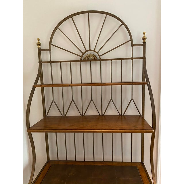 This Bakers Rack fits into a variety of decors and rooms. It has a wrought iron frame with brass finials and a cimarron...