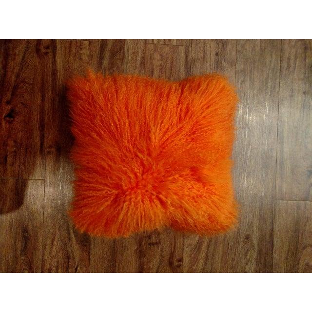 New showroom display orange Gambrell Renard Mongolian lamb pillow. Cotton fabric on back with zipper closure. 100%...
