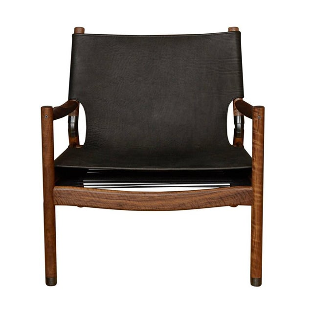 Matte black buffalo leather walnut lounge chair with blackened brass sabots and joint connectors. Designed by Ben Erickson...