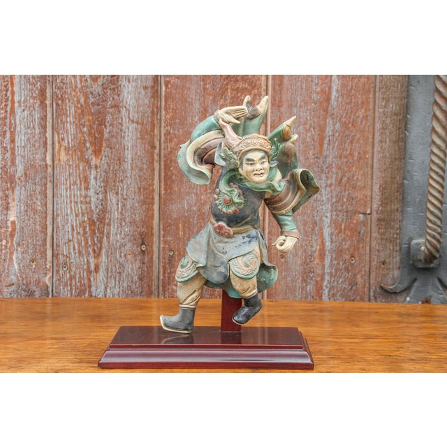 A charming vintage Chinese figurine on a wooden stand. It is an intricate ceramic trader figure in a charging stance, it...