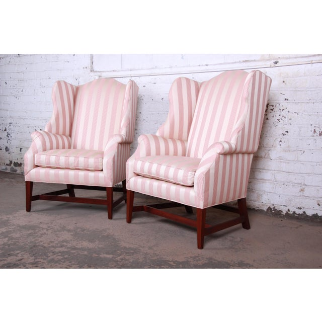A gorgeous pair of wingback lounge chairs by Baker Furniture. The chairs feature solid mahogany tapered legs, scrolled...