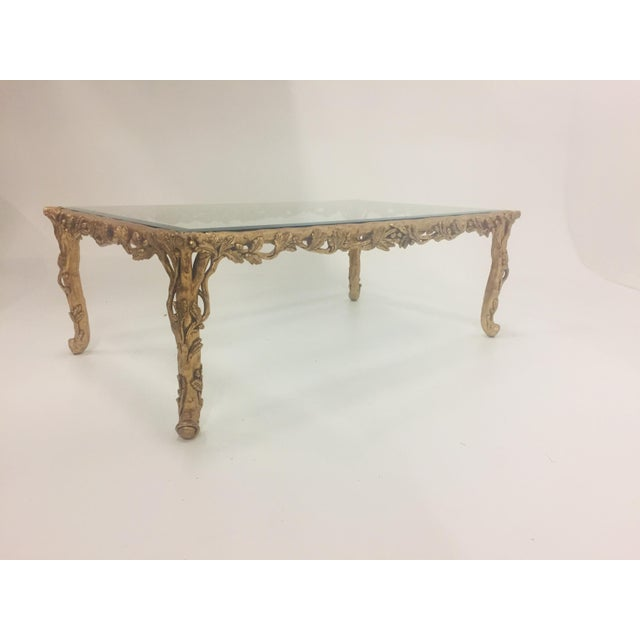 Very glamorous gilded hand carved wood rectangular coffee table having ornate leafy decoration on the base and heavy...