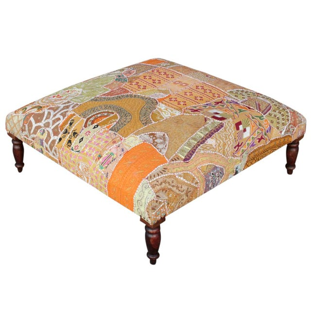 Ottoman with wood frame upholstered in vintage hand-sewn tapestry fragments from Gujarat, India. Some wear.