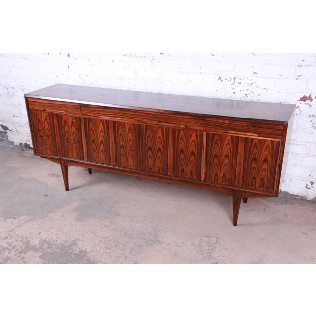 Offering an exceptional rosewood Danish Modern sideboard credenza. This Scandinavian piece has fantastic wood grain and is...