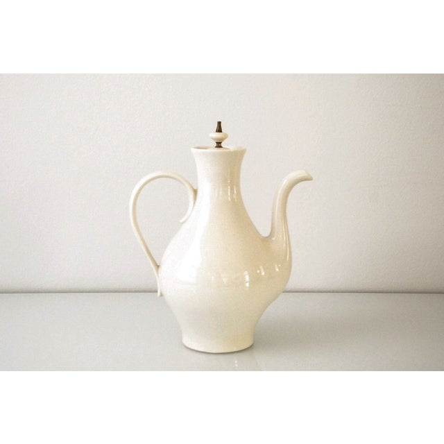 This Mid-Century Modern porcelain coffee pot from the 1960s that has a minimalist design with sleek, elegant lines and...
