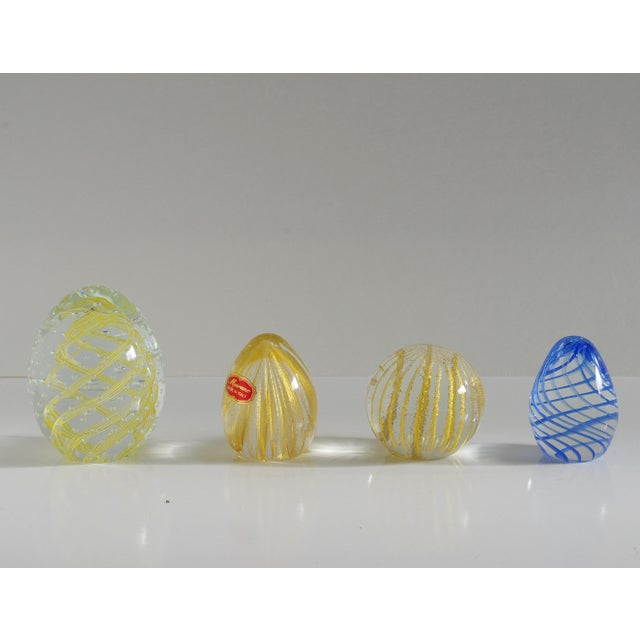 Collection of four paperweights made with clear, gold, and blue Murano glass hand blown in beautiful stripped patterns....