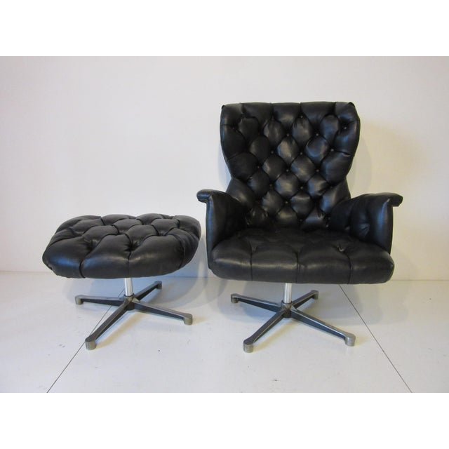 A black leatherette with diamond tufting lounge chair and matching ottoman with cast aluminum star swiveling , locking and...