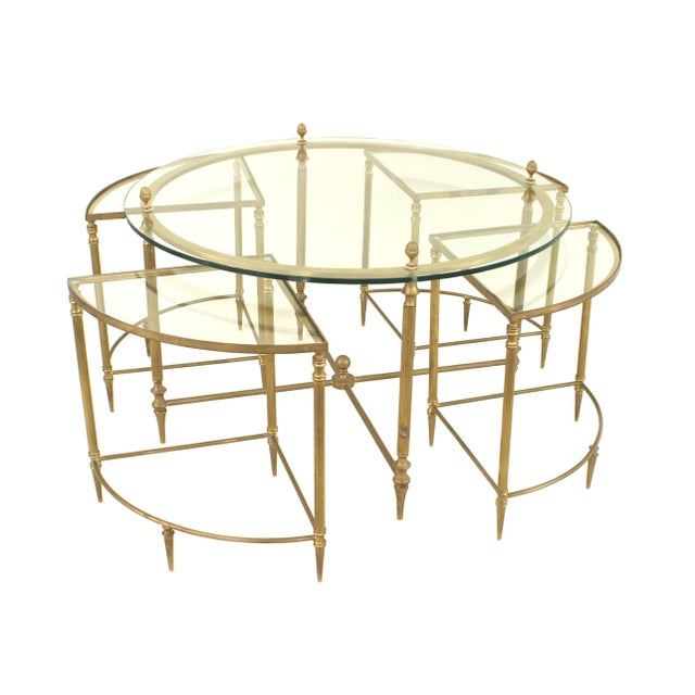 Mid-century American brass round coffee table with a glass top supported by acorn finials and a lower stretcher which fits...