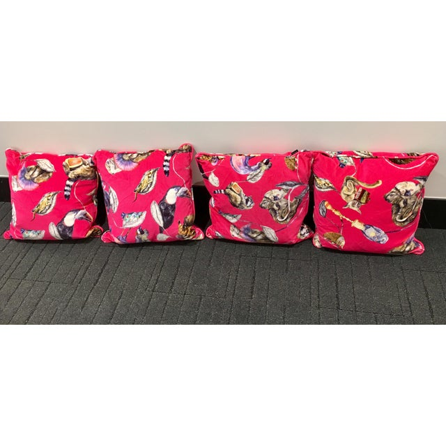 Four luxury, unused British velvet cushions that feature a carnival of animals over a statement pink background. They are...