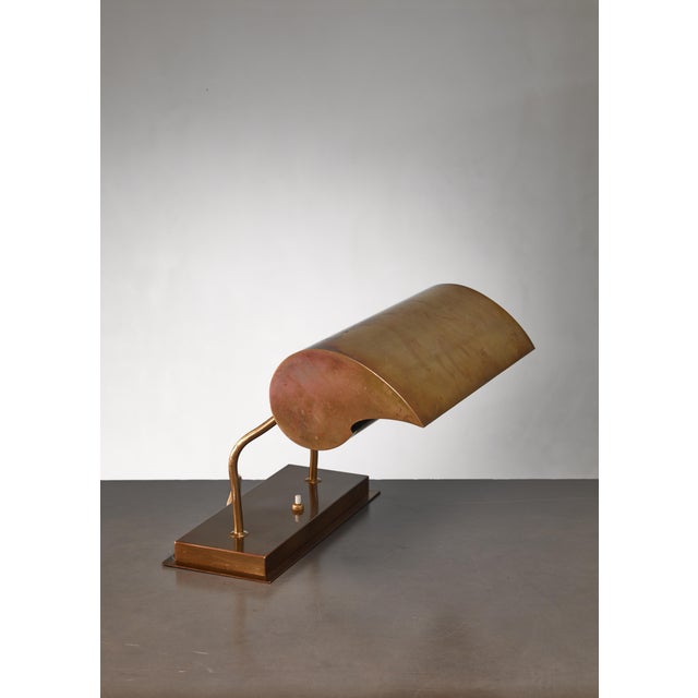 A brass table or desk lamp by Angelo Lelli for Arredoluce. The reading lamp has an adjustable 'eccola' shaped shade with...