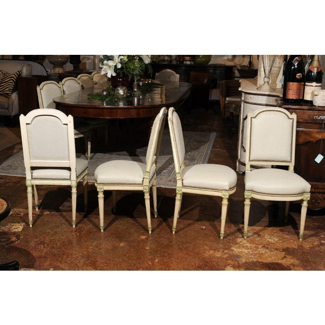 A set of eight French Louis XVI style dining room side chairs from the 19th century, with new upholstery and fluted legs....