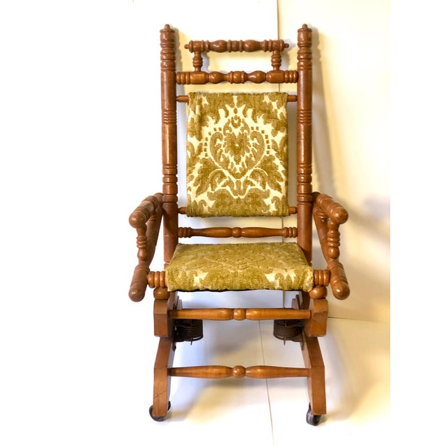 This funky little antique child's rocker was made during the late 19th Century and is made of maple with a spool design...