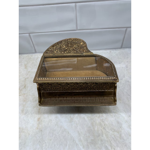Lovely vintage brass filigree grand-piano shaped jewelry box with music. Beautiful filigree detailing, with only a few...