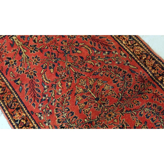 Antique hand made Persian Sarouk runner in red wool and floral design. The rug made in 1900s and it is in original good...