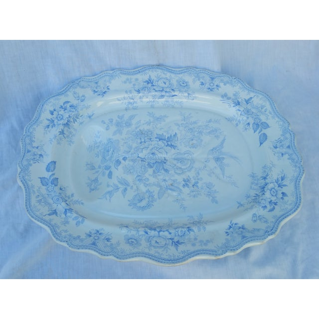 A Victorian-era, Staffordshire carving plate with a well to catch juices. Made in England. Features a softly faded, blue...