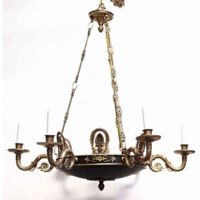 Empire style brass chandelier with wreath and crest details, a black and gold finish and six candlestick arms. These...