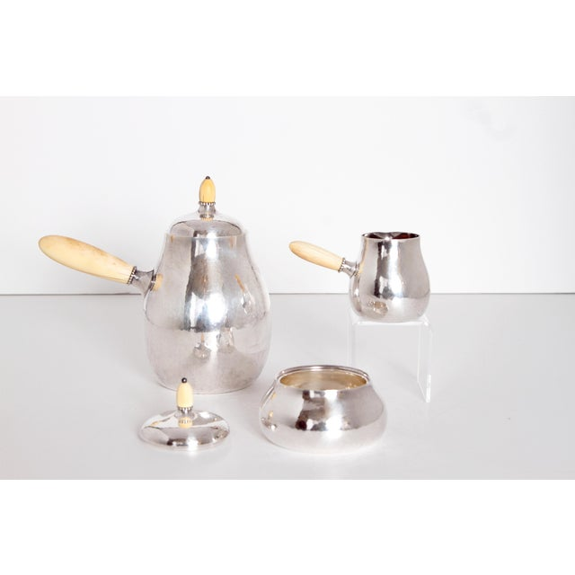 A Georg Jensen coffee set of silver with pot, sugar and cream jug. Bone handles and finials on lids. Stamped A. E. F....