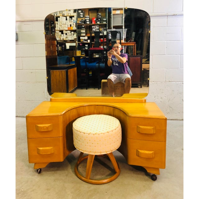 Vintage 1950s Heywood Wakefield maple wood vanity with mirror and foot stool set in the champagne finish. The vanity has 4...