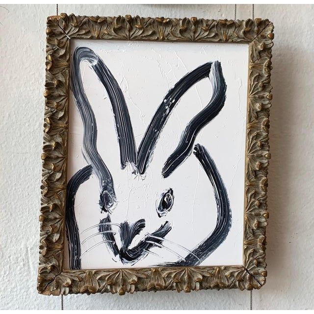 Classic and perfect white and black bunny by Hunt Slonem. So much personality! The painting is framed in a vintage carved...