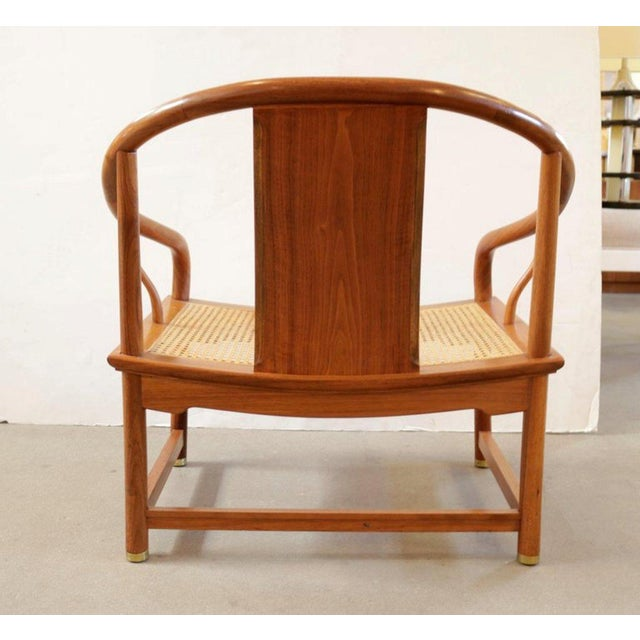 Horseshoe shape caned chair made of blond mahogany by designer Michael Taylor's for Baker Furniture. The chair retains the...