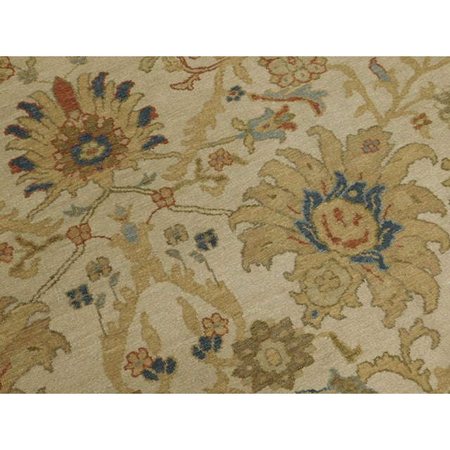Hand knotted. Wool pile on cotton foundation. Stylized flowers on beige Background within beige border decorated with turtle.