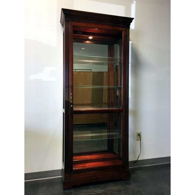 This cabinet features decorative carved molding on the profiled pediment, and reeded columns with wooden column caps frame...
