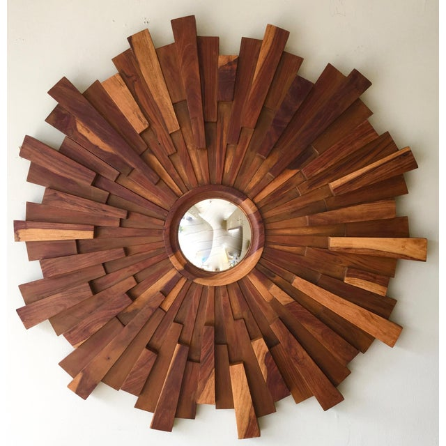 This is a small convex mirror encased in a large sunburst pattern of beautiful wood pieces. It is more art than a mirror.