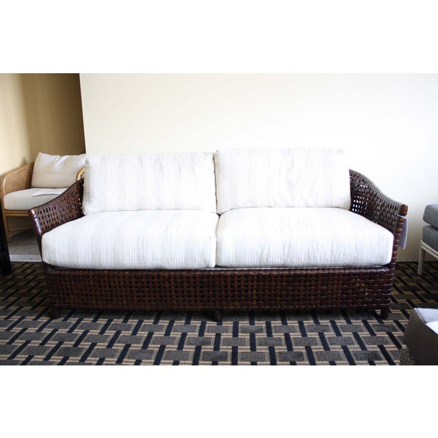 """A casual yet classic """"Antalya"""" sofa with a dark tobacco finished frame, with woven rawhide accenting. The back and seat..."""