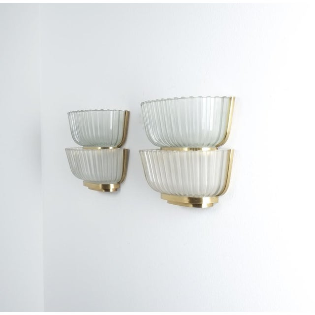 Pair of late Art Deco glass and brass sconces refurbished, Italy, circa 1940. Featuring 2 thick molded glass screens or...